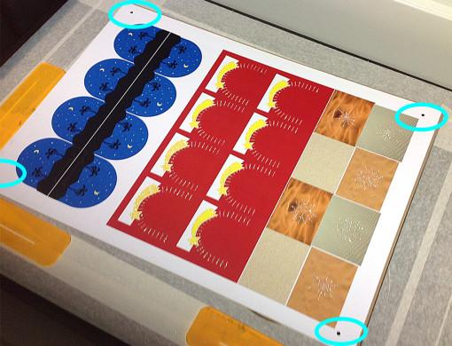 Il substrato è posto in modo non preciso sul piano della macchina. I «pallini» hanno lo scopo di far in modo che la telecamera rilevi la loro posizione e il laser si adatti di conseguenza.